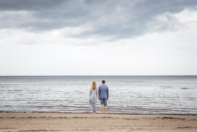 man and woman standing on shore holding hand zoom background