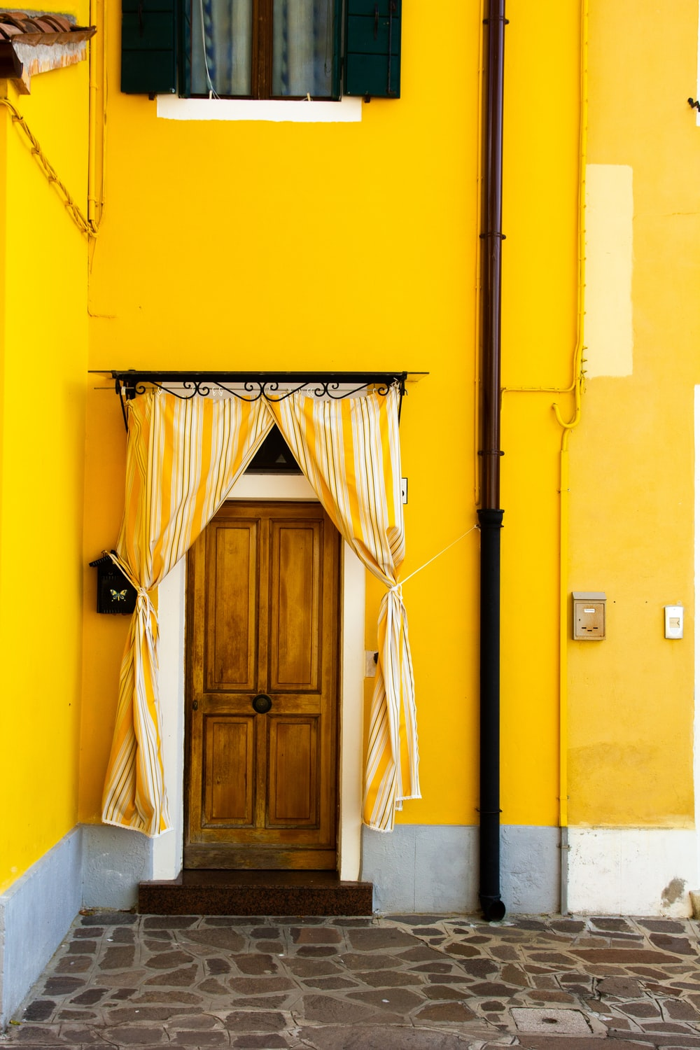 yellow paint house with brown wooden door