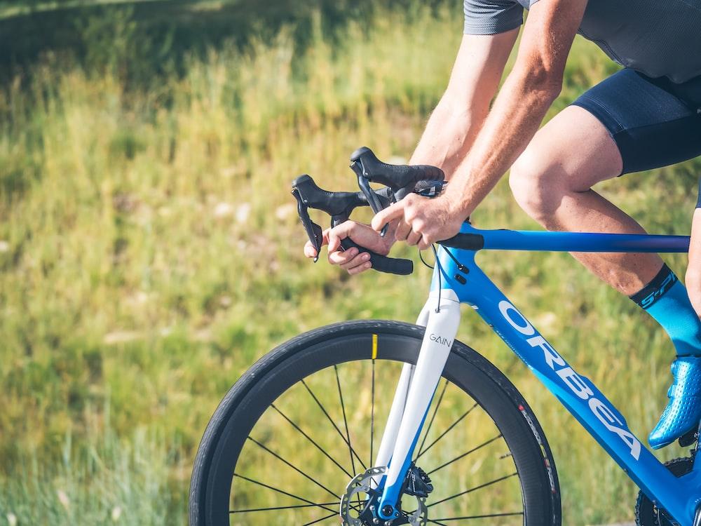 man riding road bike during daytime