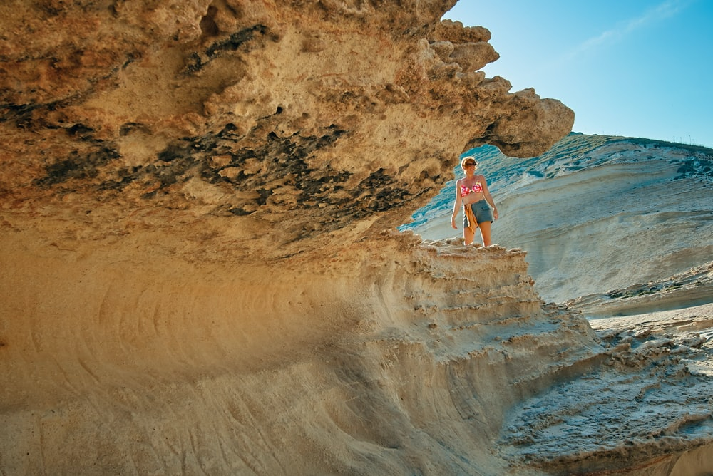 woman standing near brown rock formation under clear blue sky
