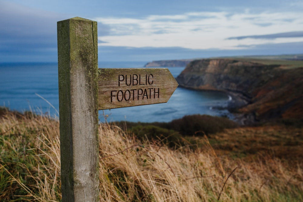 Public Footpath concrete road signage surrounded by grass during daytime