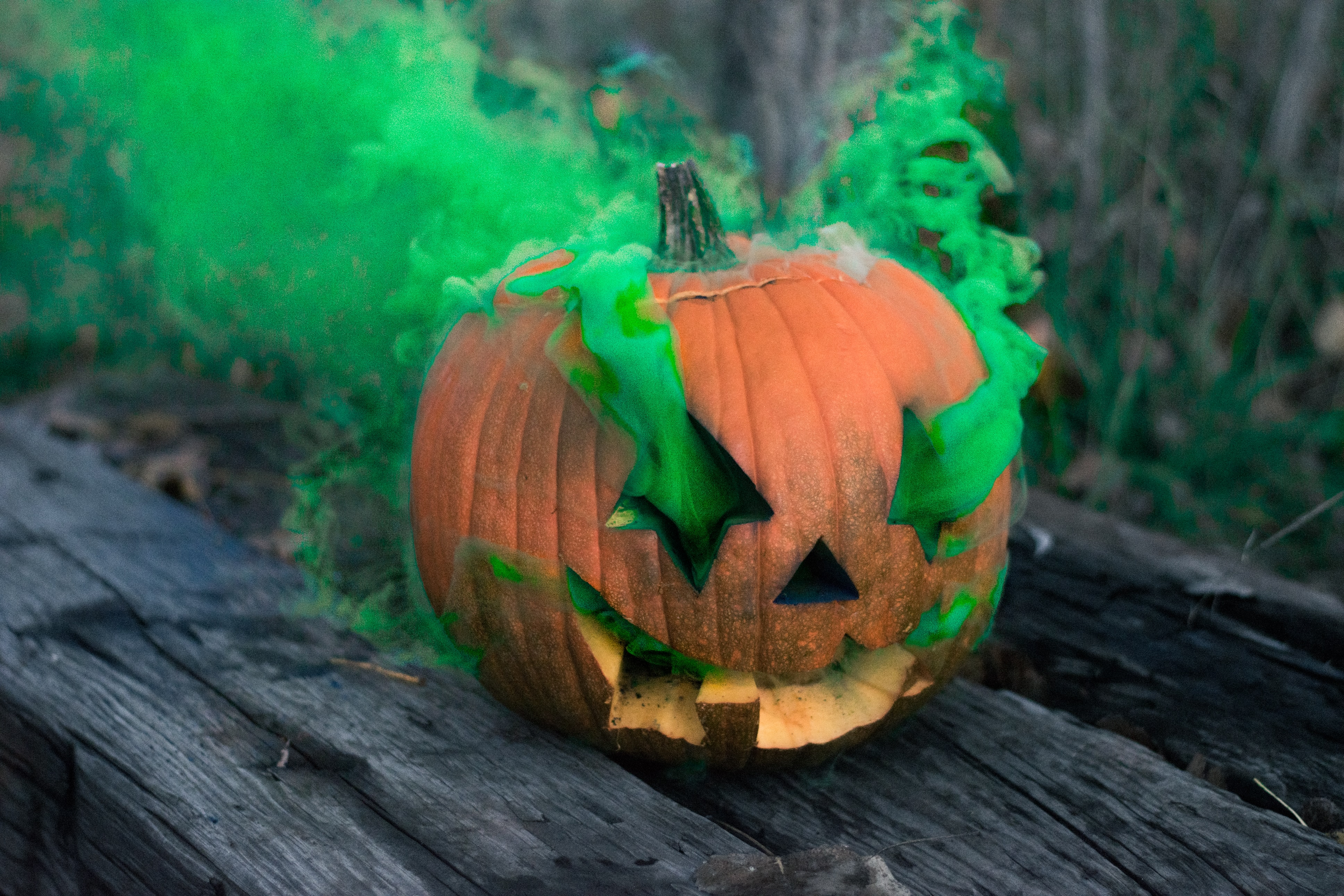 Jack-o'-lantern releasing green smoke on grey wooden board