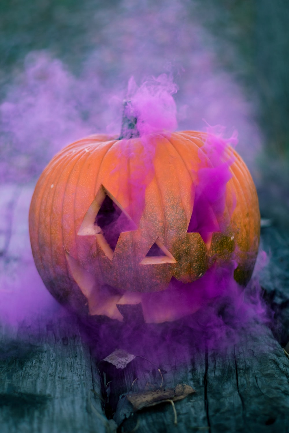 orange Jack-o'-lantern with pink smoke on gray wooden surface