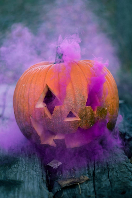 orange Jack-o'-lantern with pink smoke on gray wooden surface