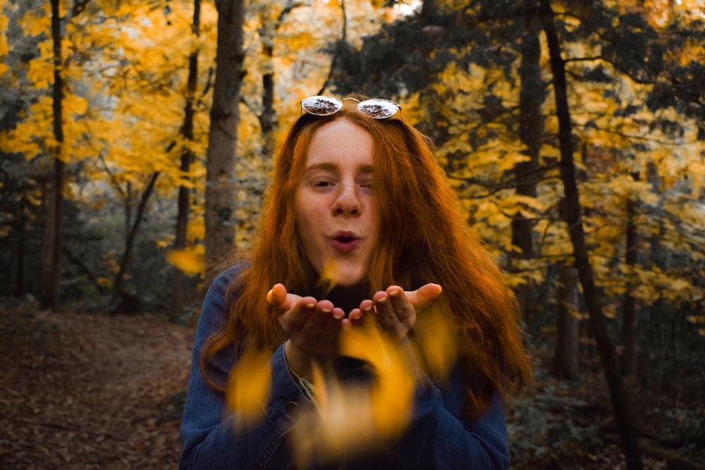 woman blowing near tree