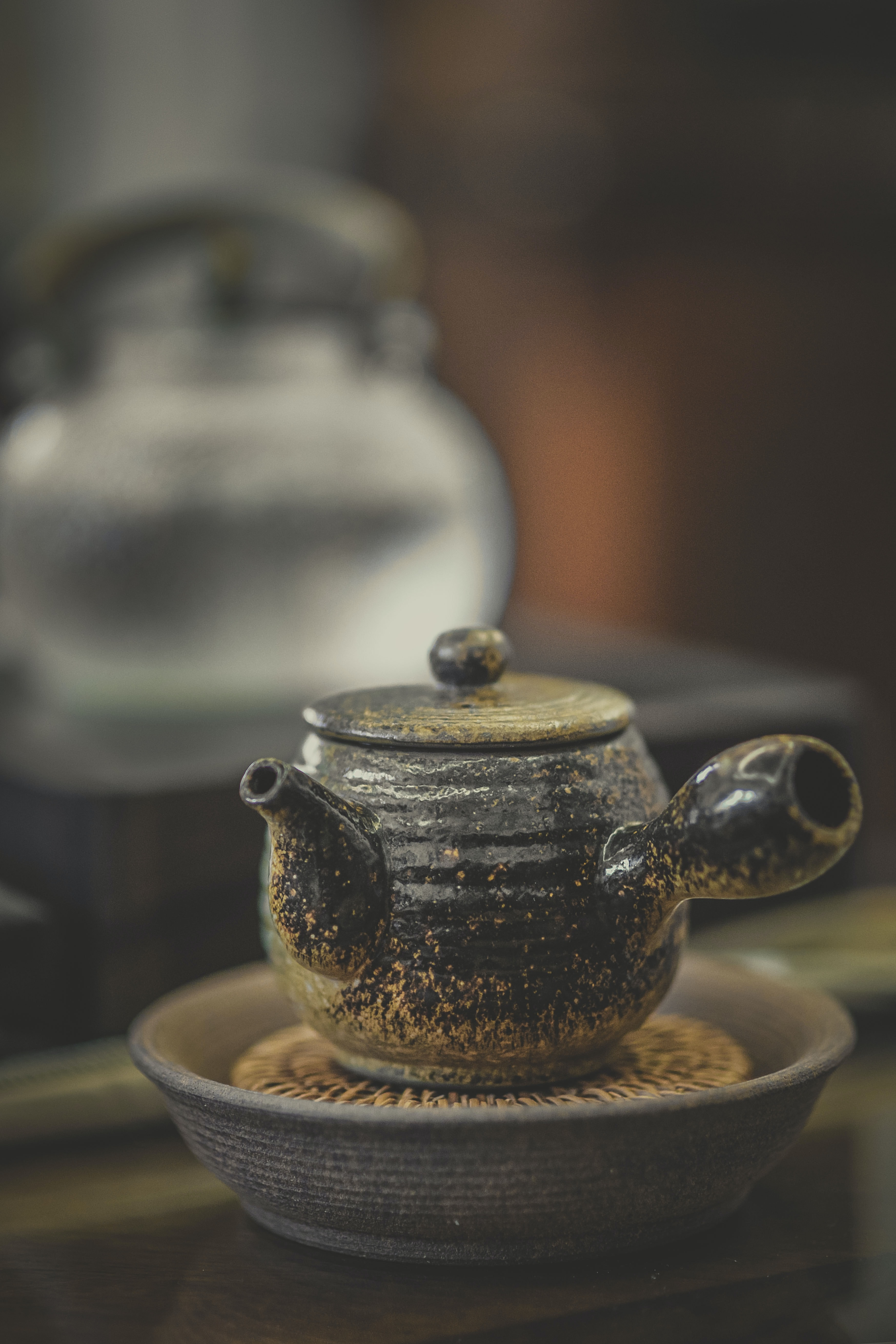 close-up photography of black ceramic pot on brown surface