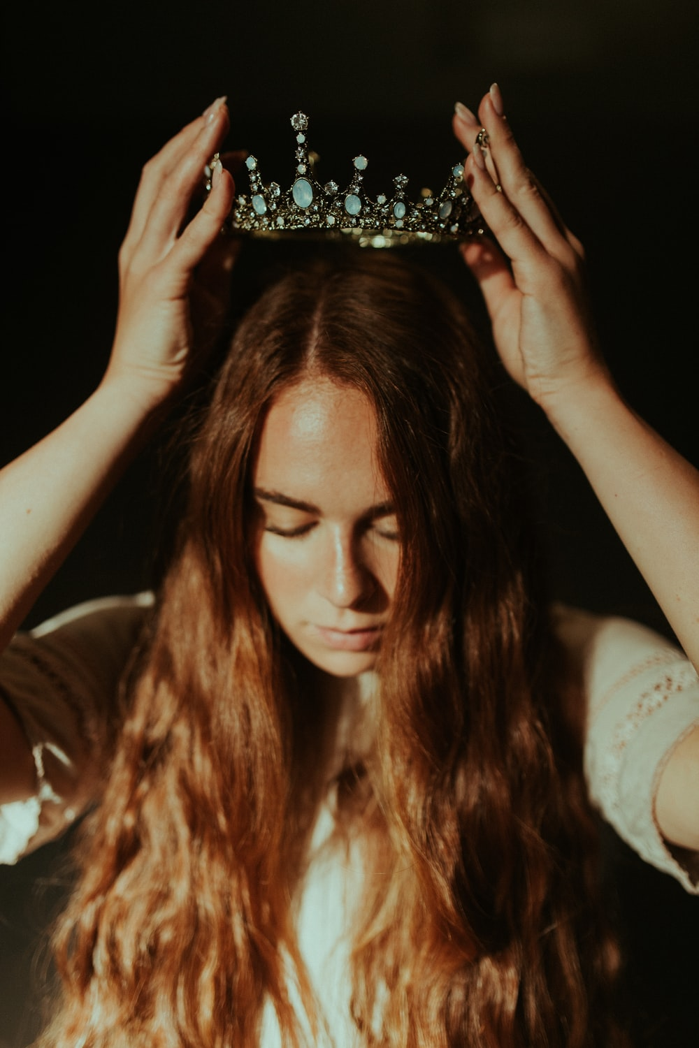 woman putting silver-colored tiara on her head