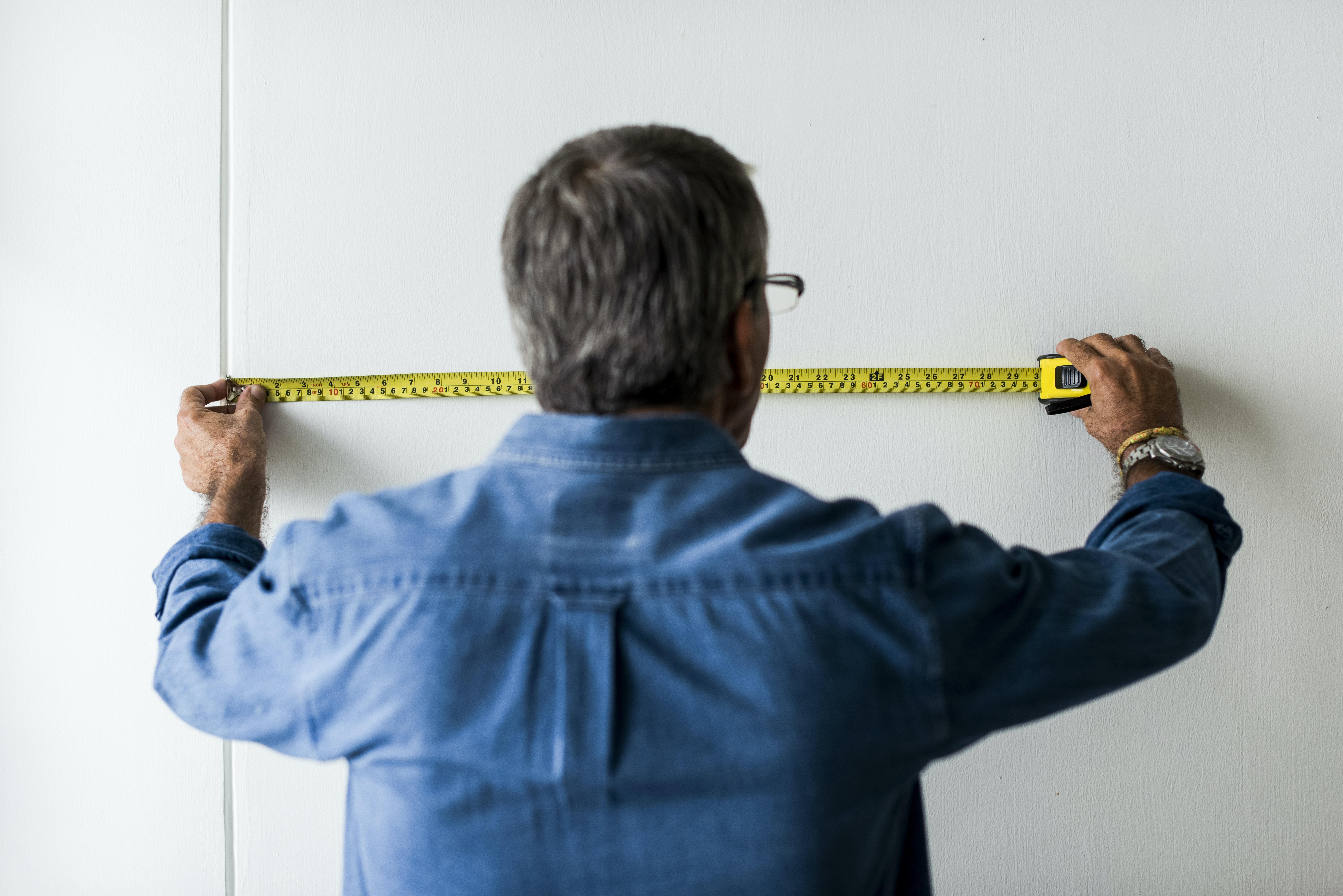 man holding tape measurer