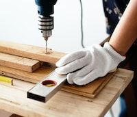 person drilling on wood plank