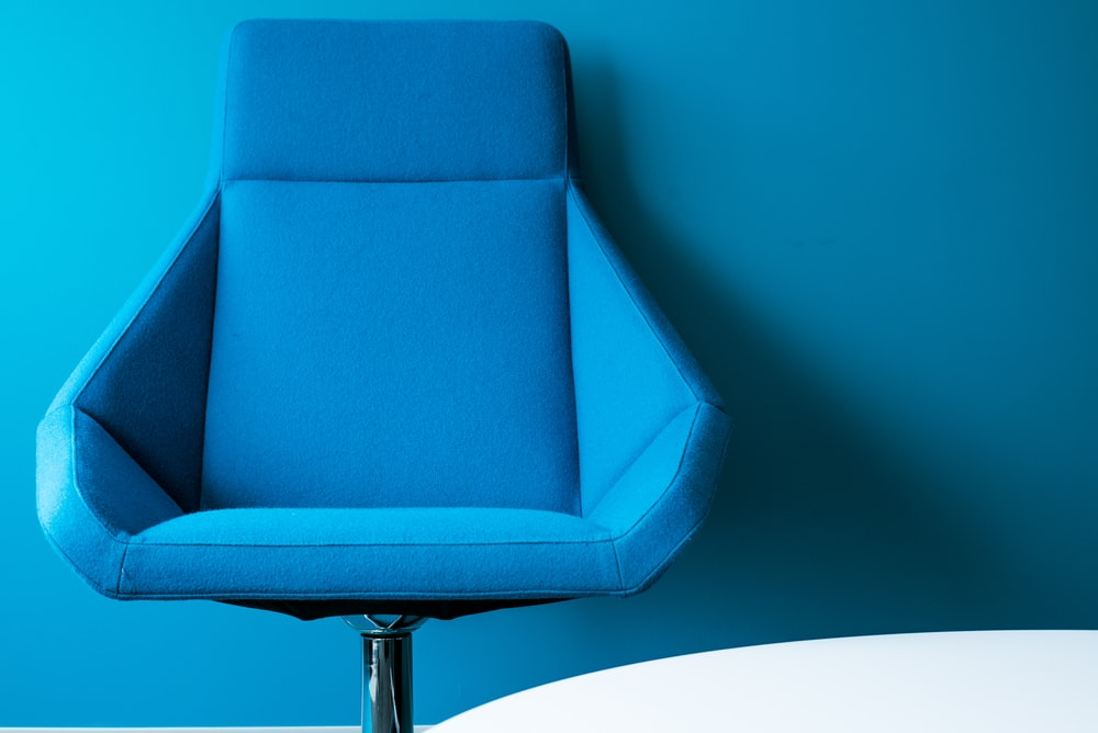 blue padded swivel chair leaning on wall