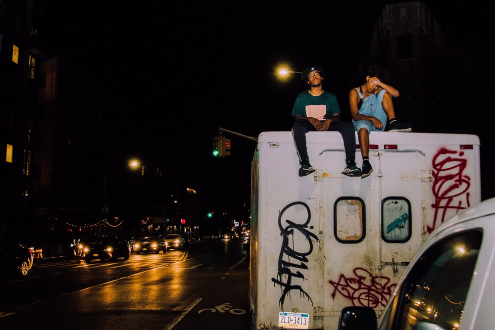 two man sitting on top of truck