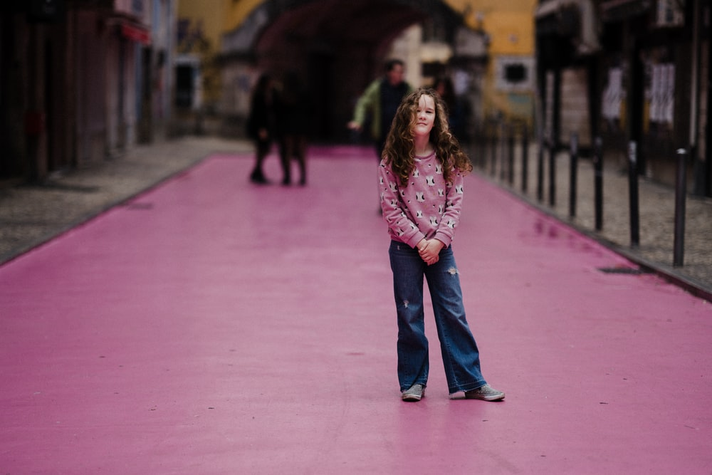 selective focus photography of girl on purple street