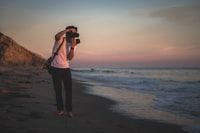 man taking photo of seashore