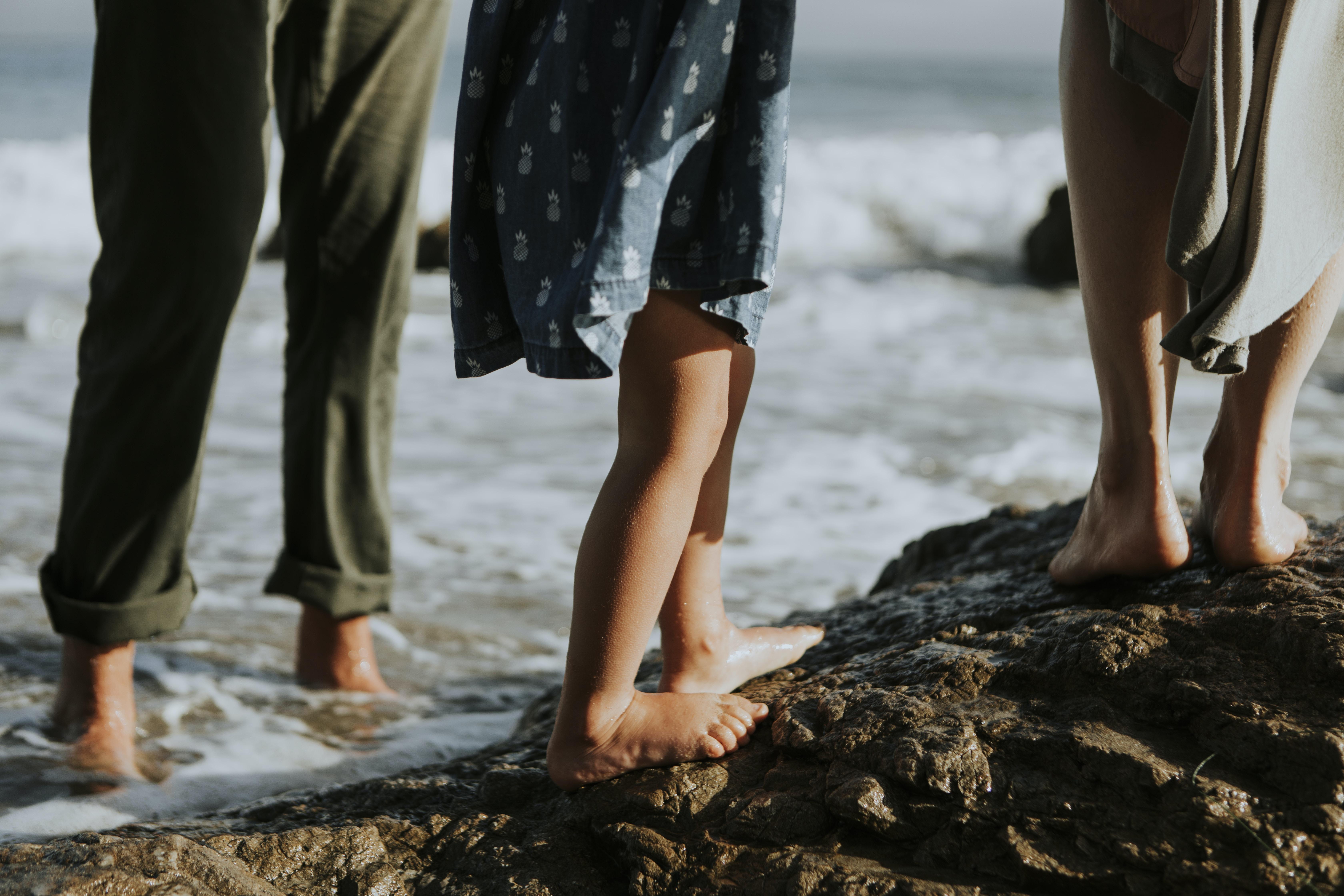three person standing on rock near seashore