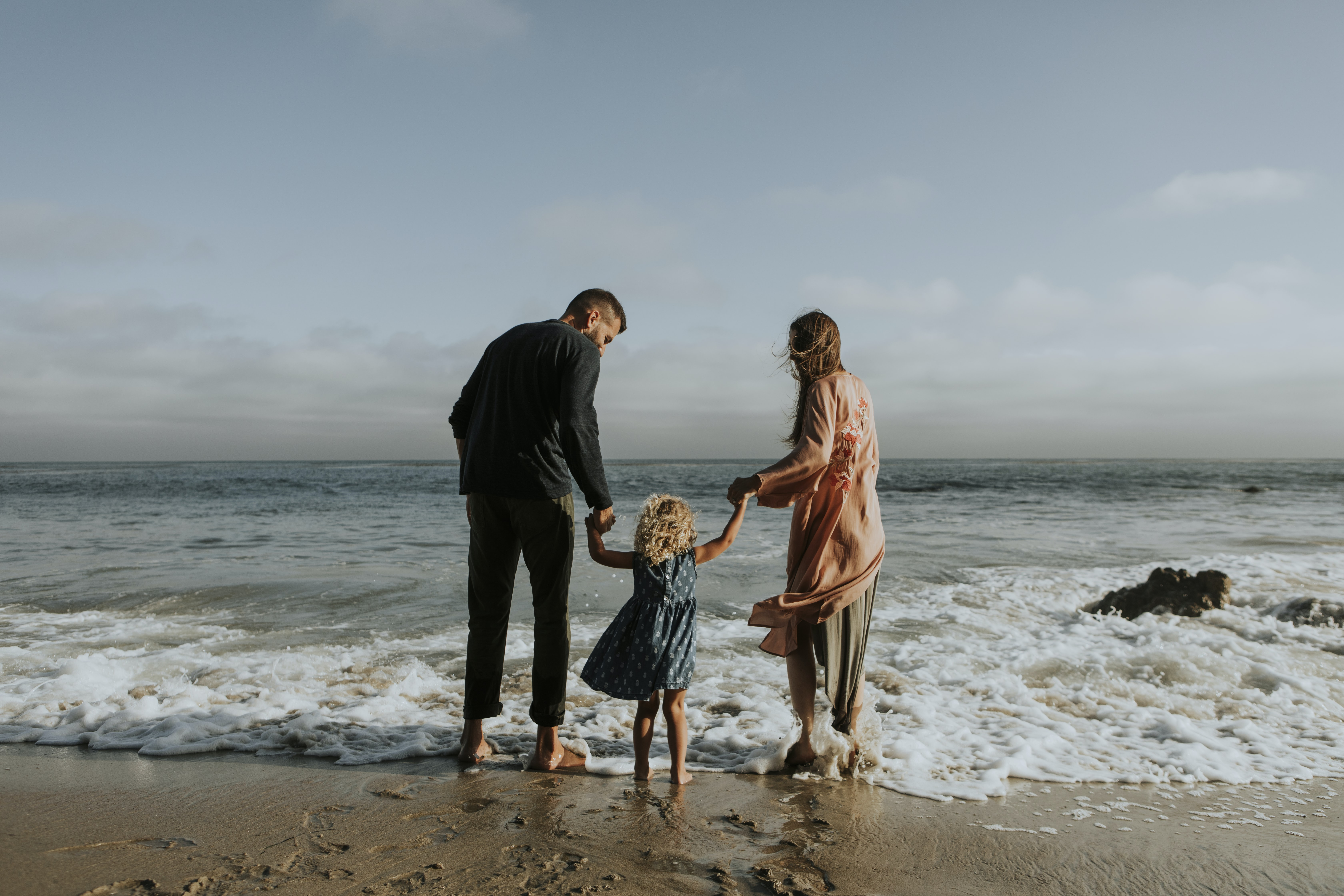 man, woman and child standing on seashore during daytime