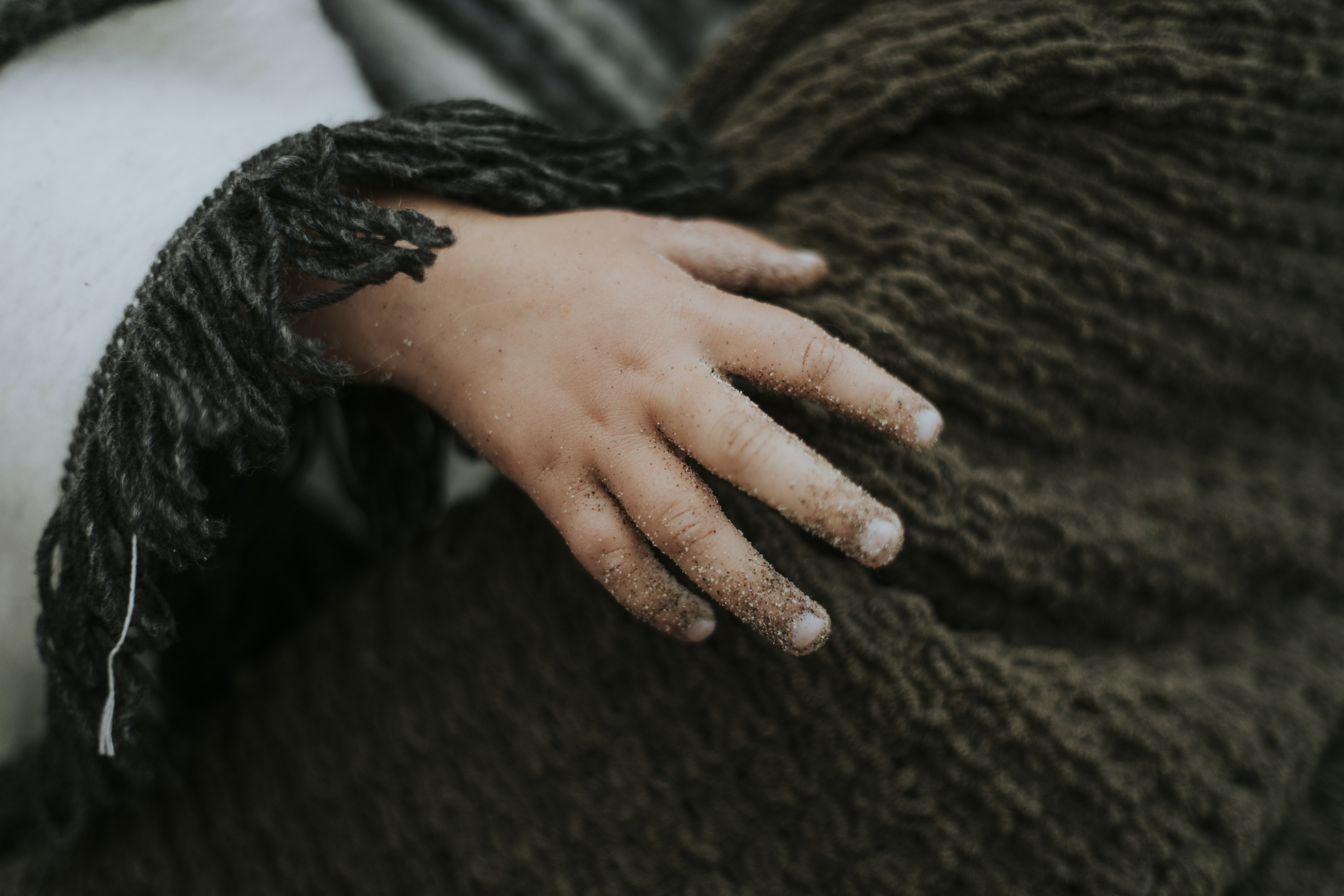 person holding on gray crochet textile