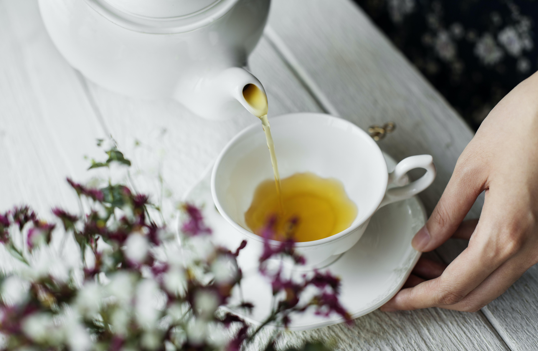 person pours tea in ceramic teacup
