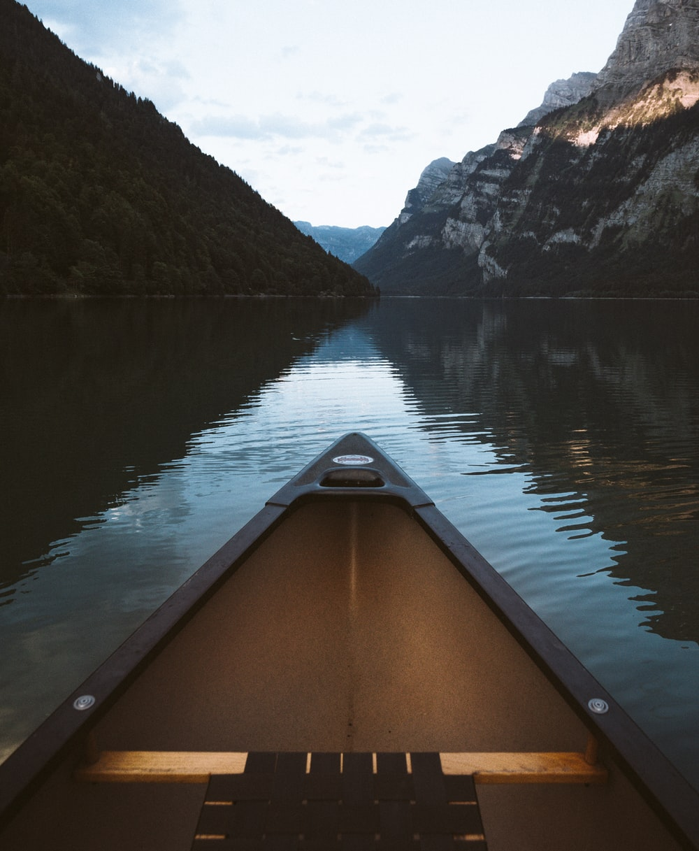 canoe on body of water with mountain background