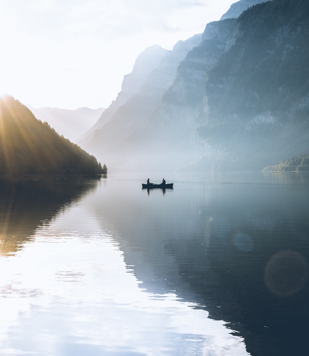 boat on body of water near rock mountains
