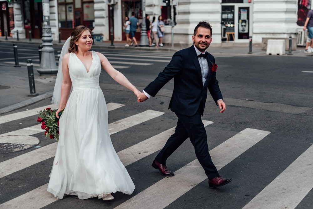coupe wearing wedding dress holding hands walking on pedestrian line during daytime