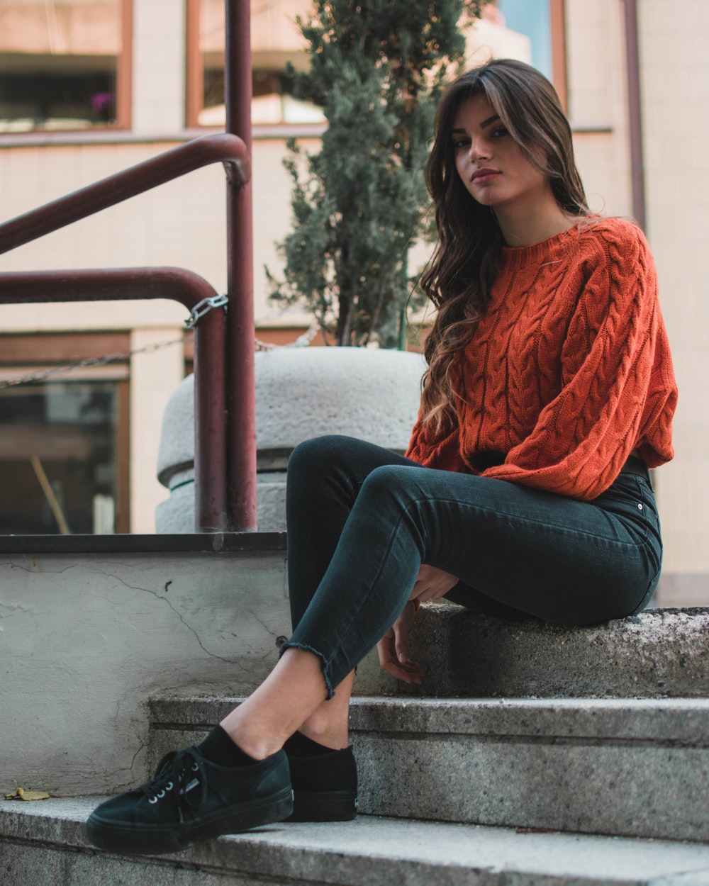 woman wearing orange crew-neck sweater sitting on the stair