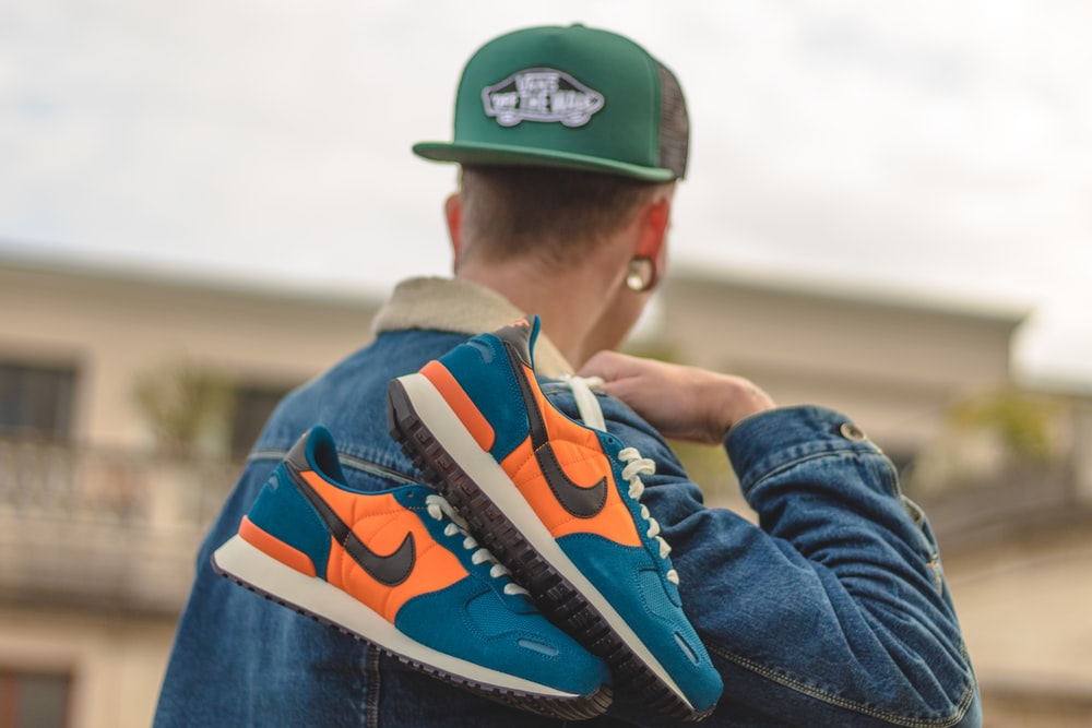 man holding pair of blue-white-and-orange Nike low-top shoes
