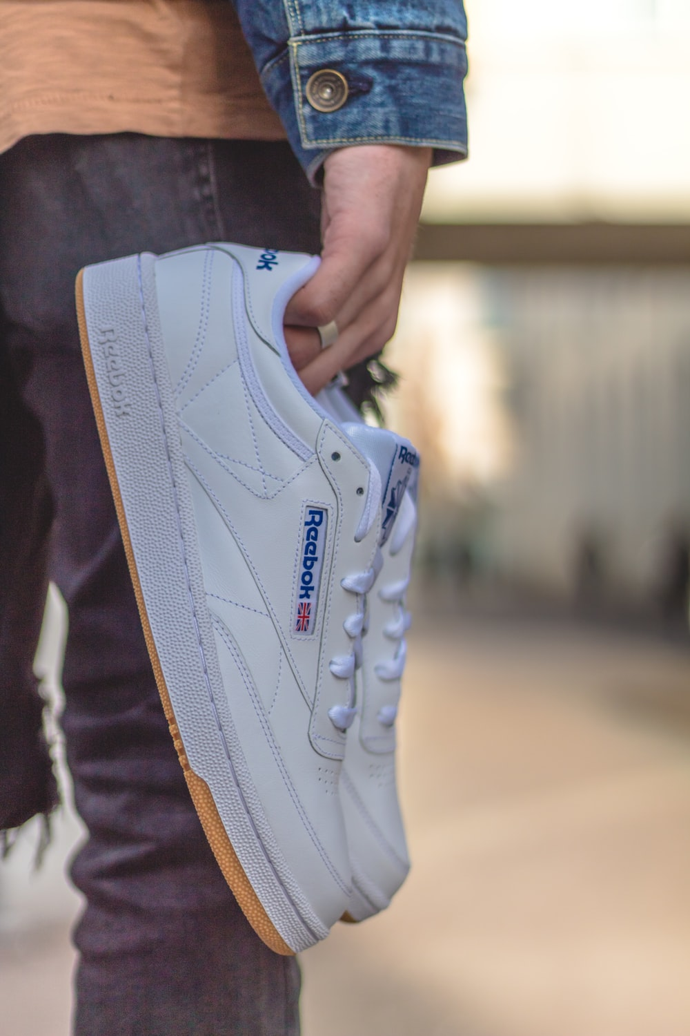 person carrying white Reebok low-top sneakers