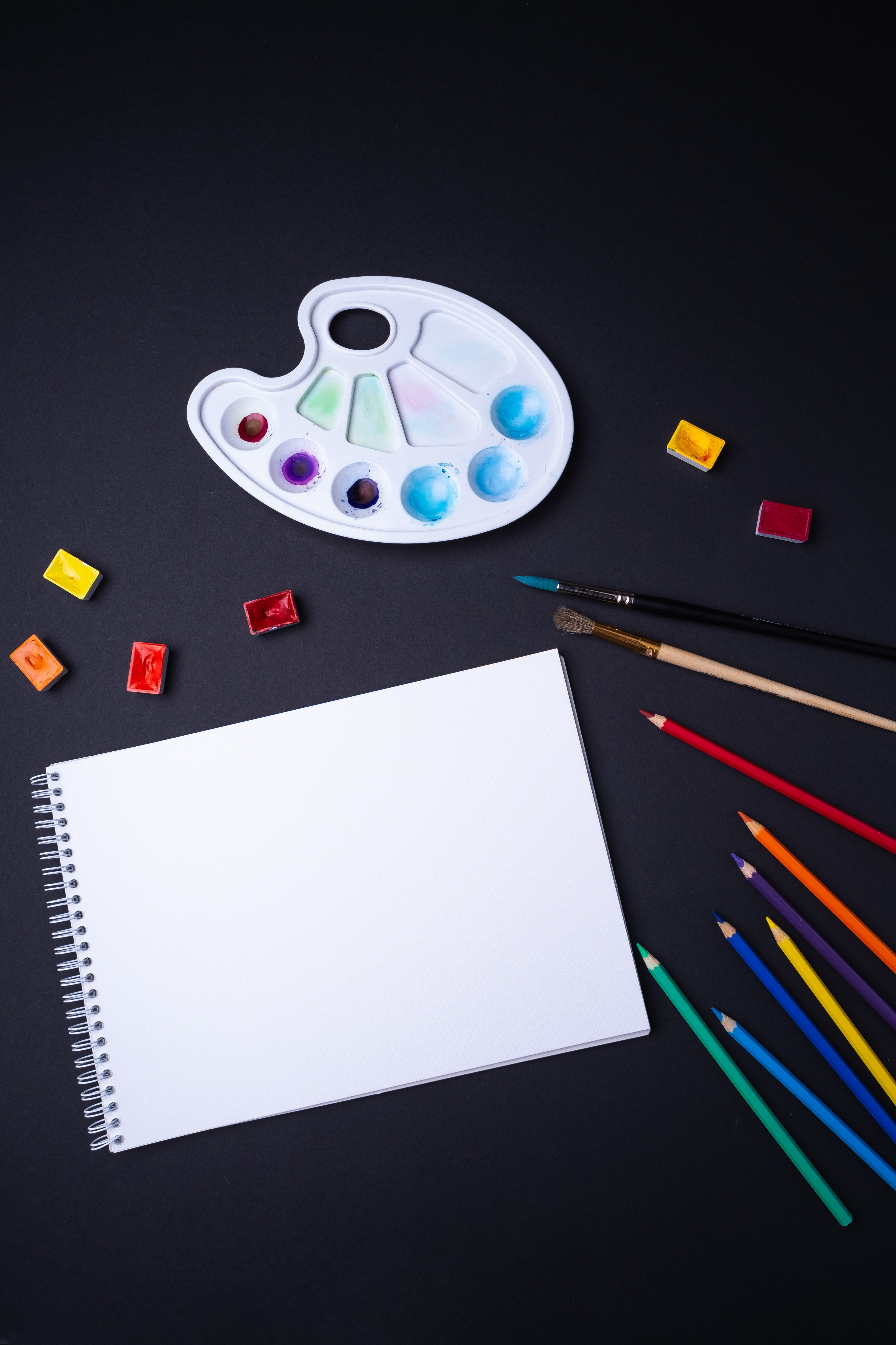 sketch pad with color pencil and paint brush