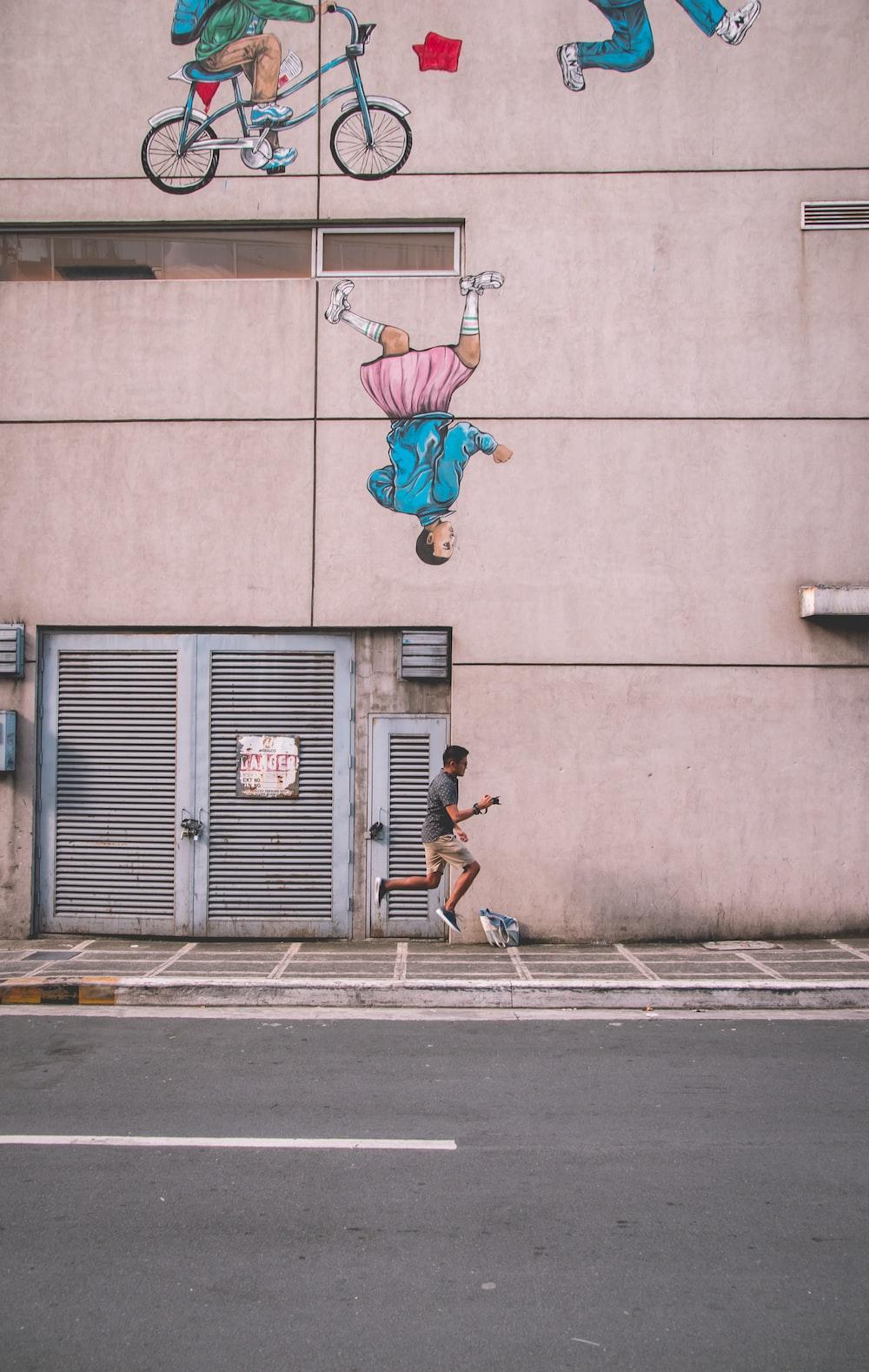 man jumping beside building during daytime