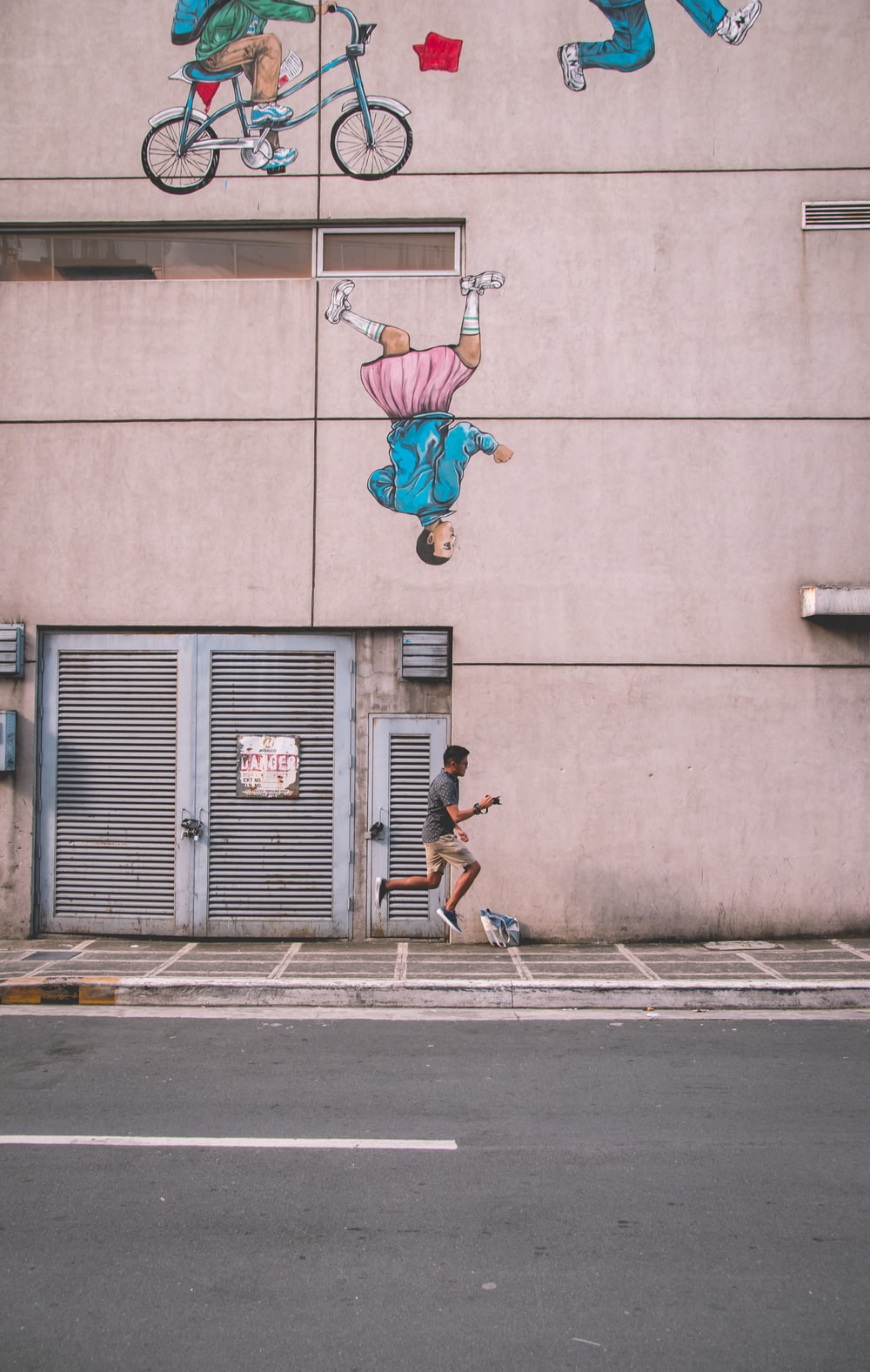 man jumping beside building during daytime