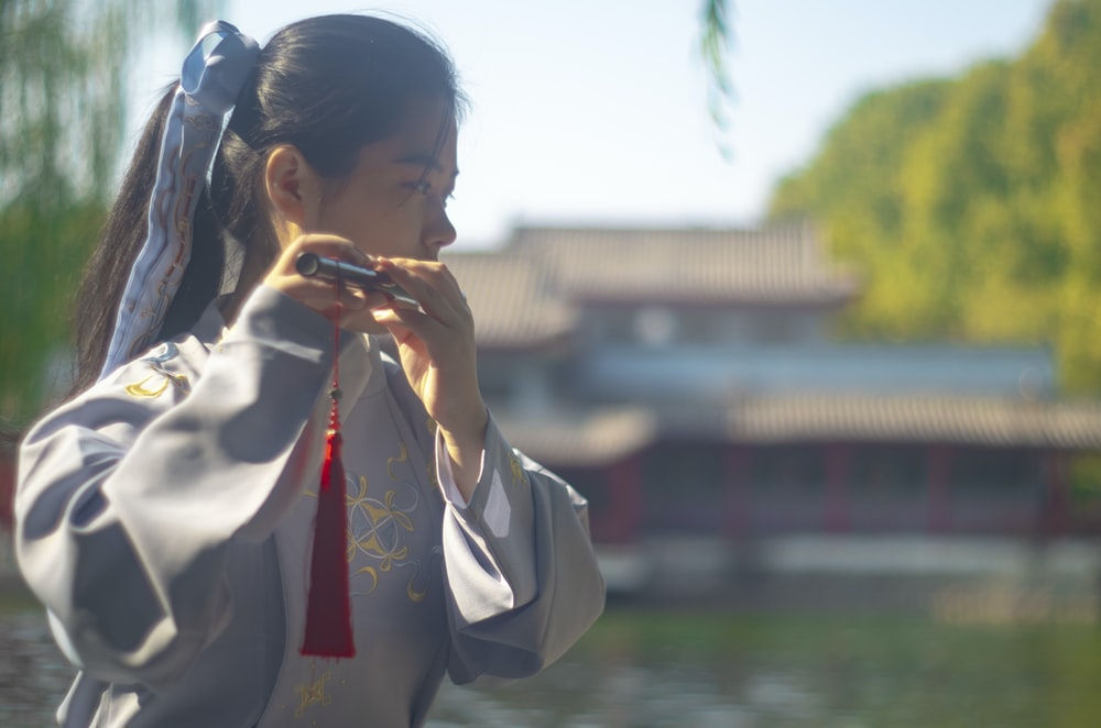 girl playing flute outdoor during daytime close-up photography