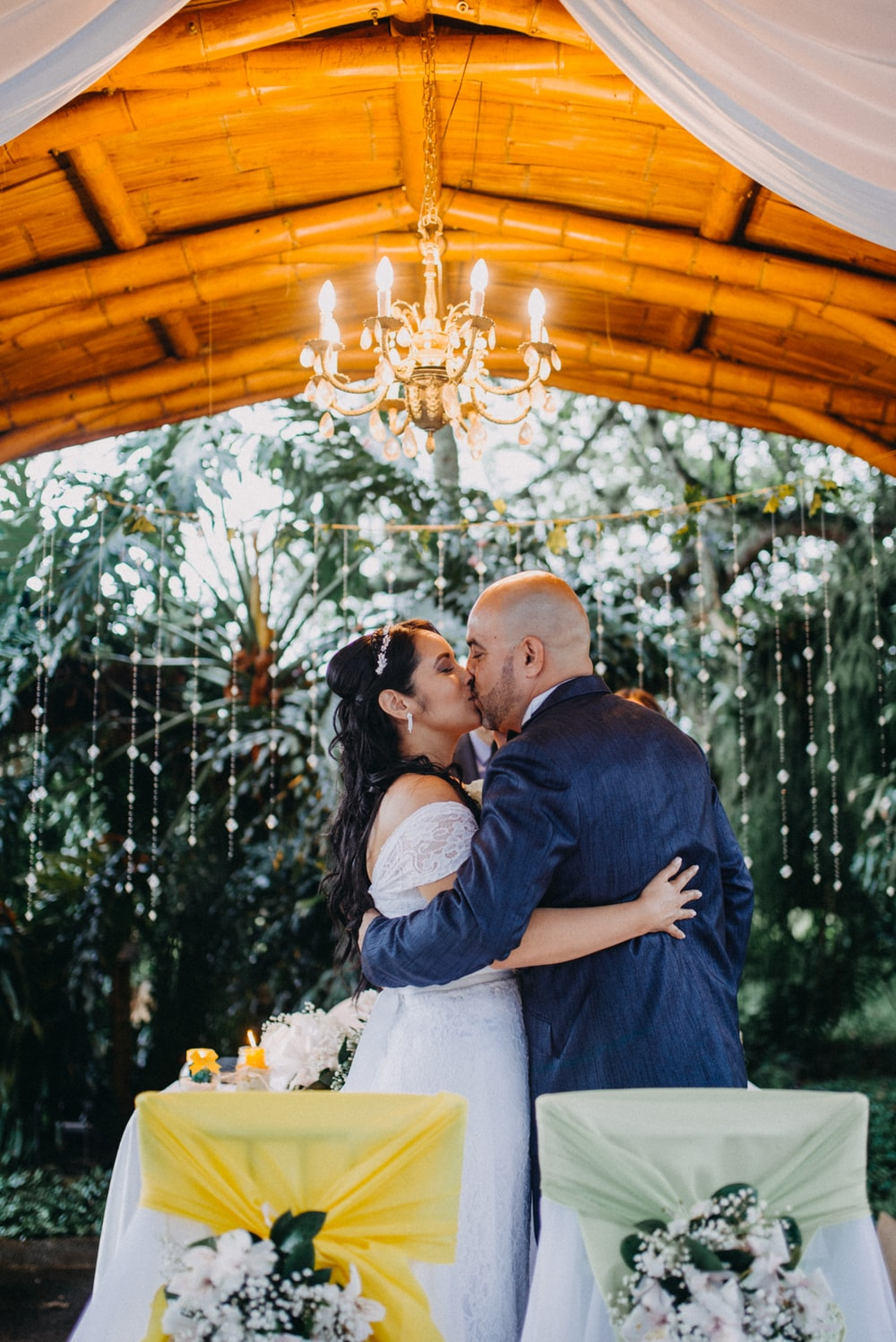 newly wed couple kissing under chandelier at reception