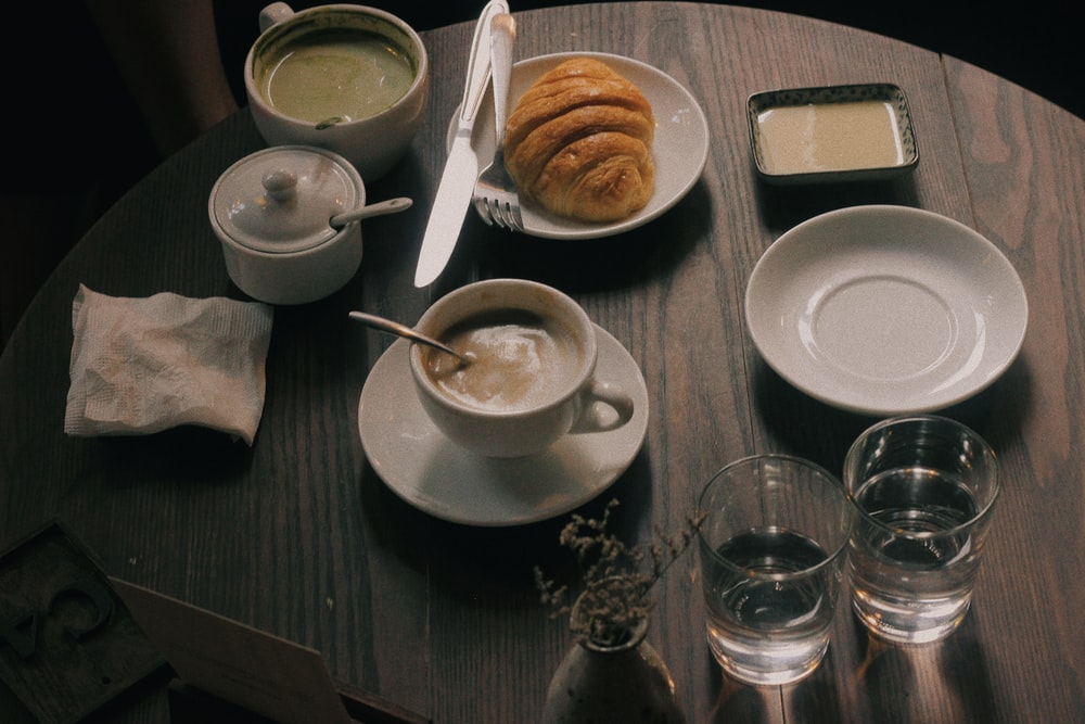 cup of coffee and bun of bread on table