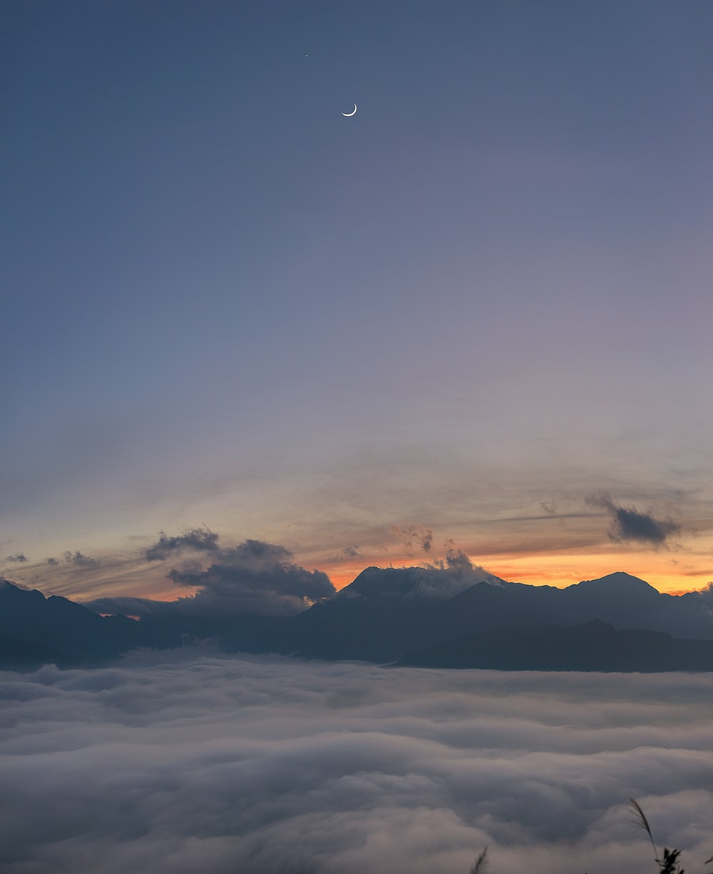 white crescent moon on blue sunset sky with clouds hovering below