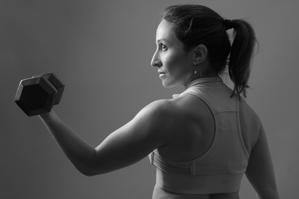 grayscale of woman carrying dumbbell