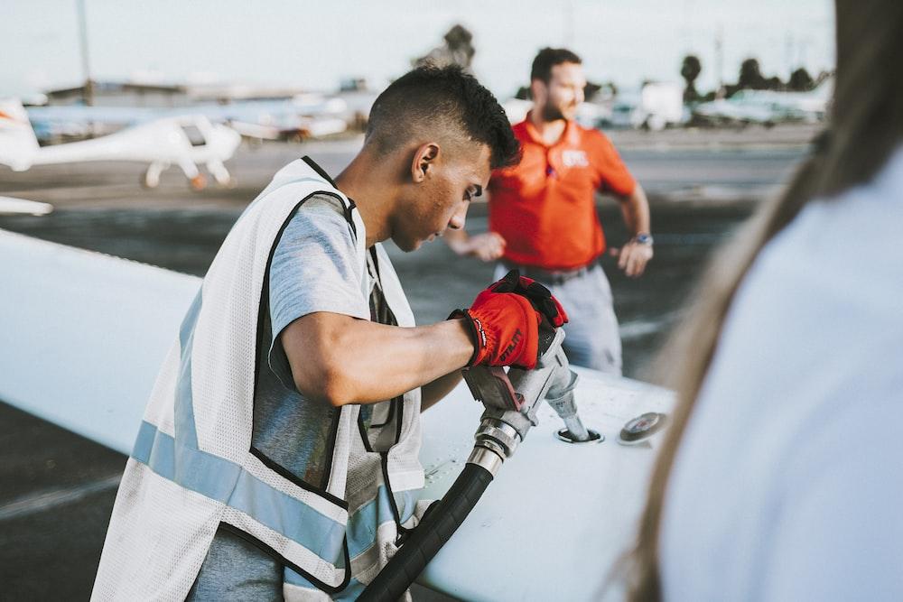 man fueling plane near man