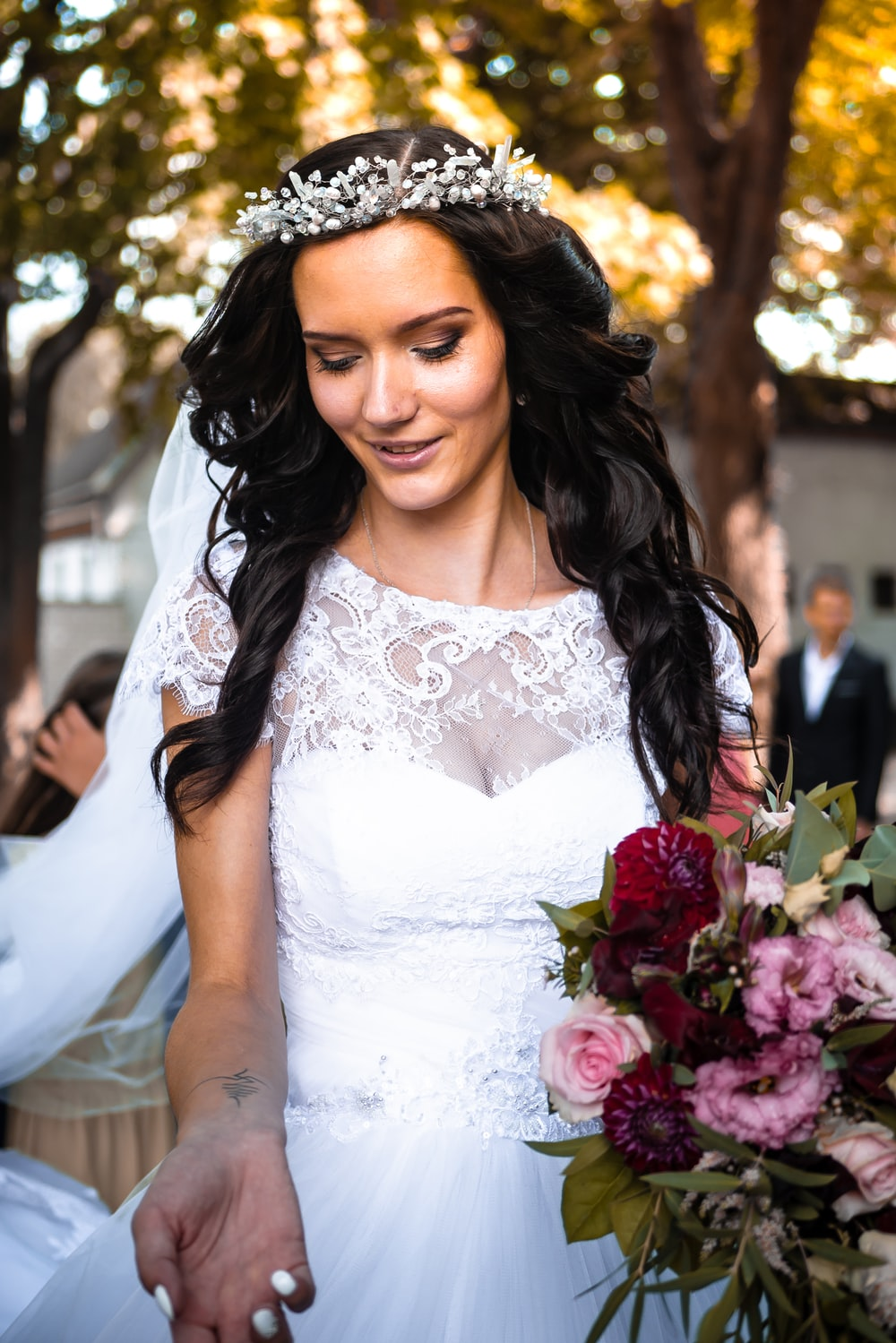 woman wearing white floral wedding dress holding flower bouquet outdoor during daytime \