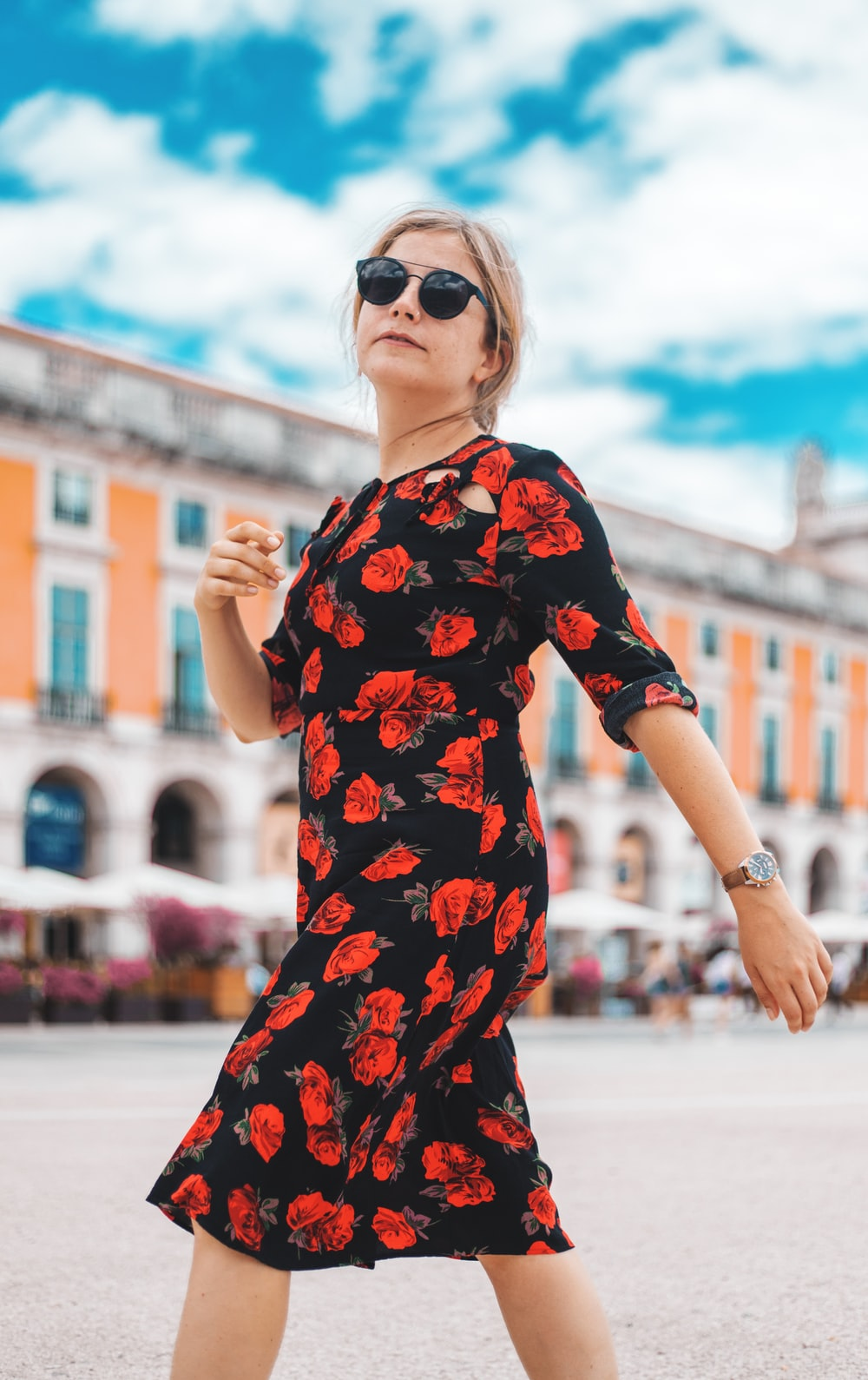 walking woman wearing red and white floral half-sleeved dress near the building during daytime