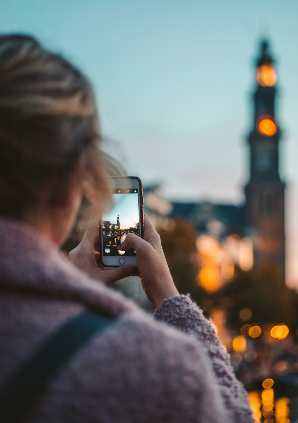 woman taking photo of a building during daytime