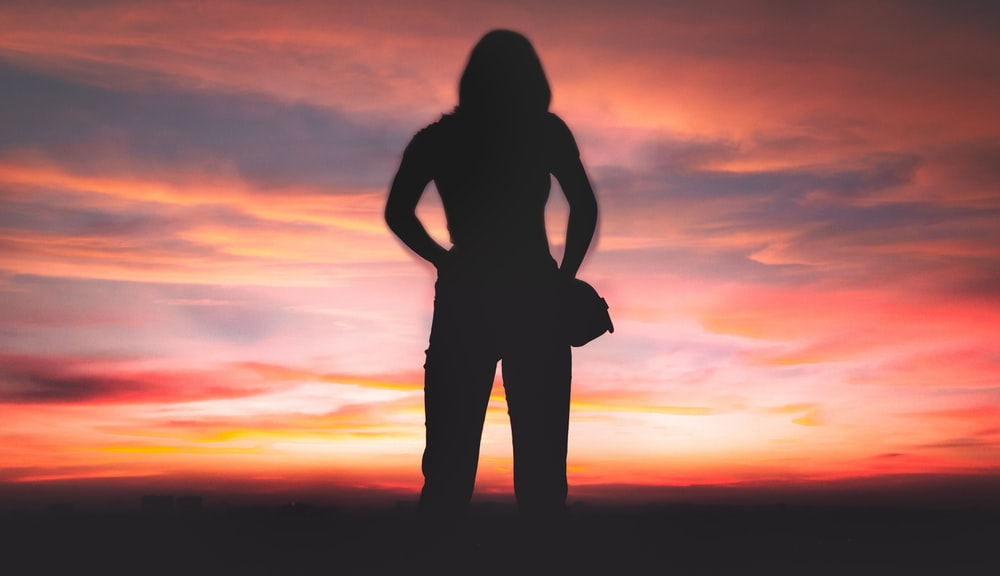 silhouette of person standing during golden hour