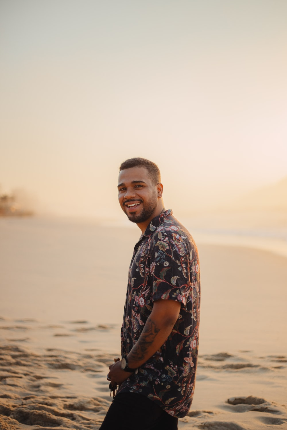 smiling man standing on sand shore during day
