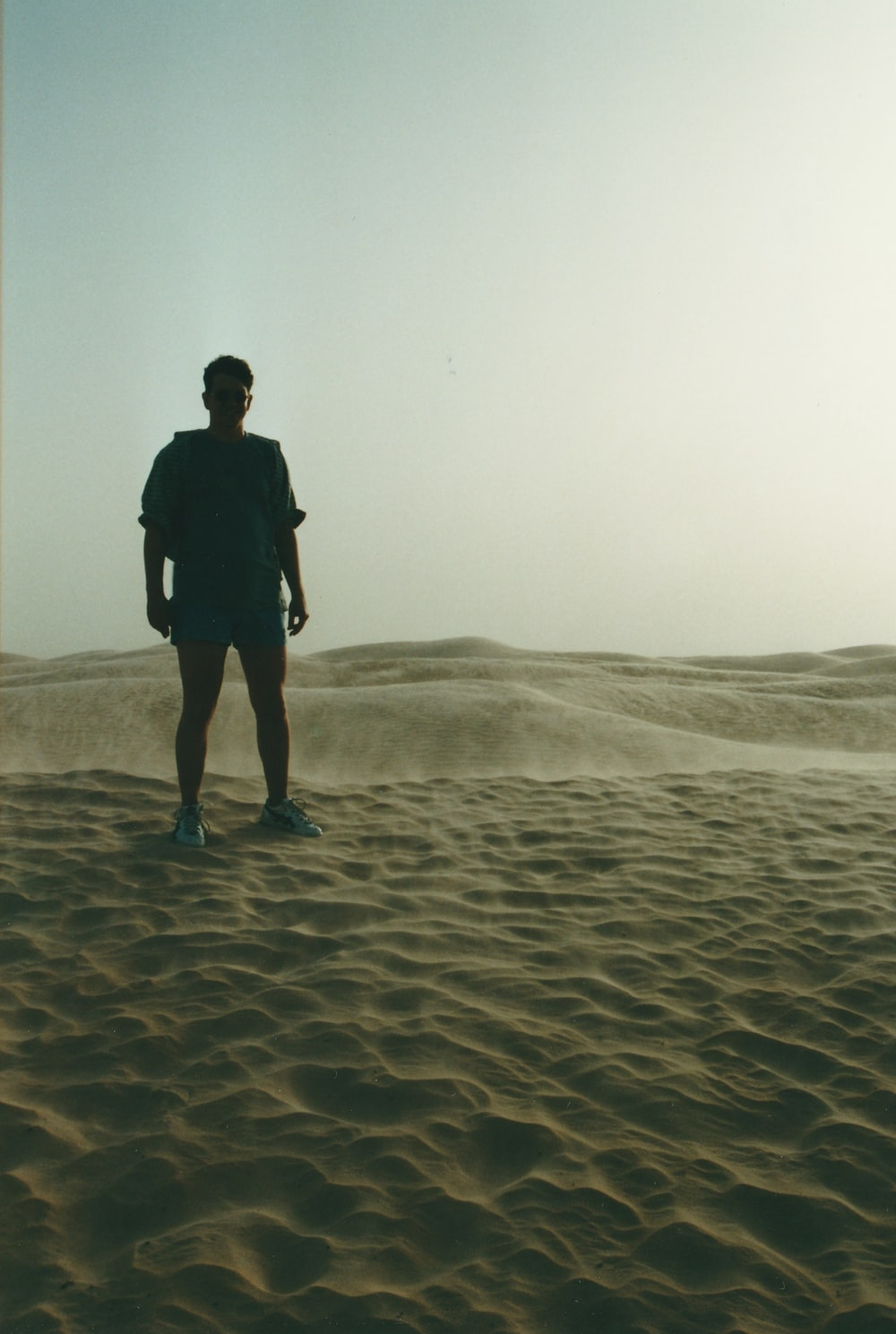 silhouette of man standing on sand
