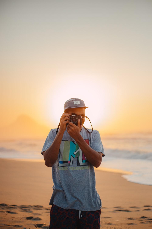 man taking photo on seashore