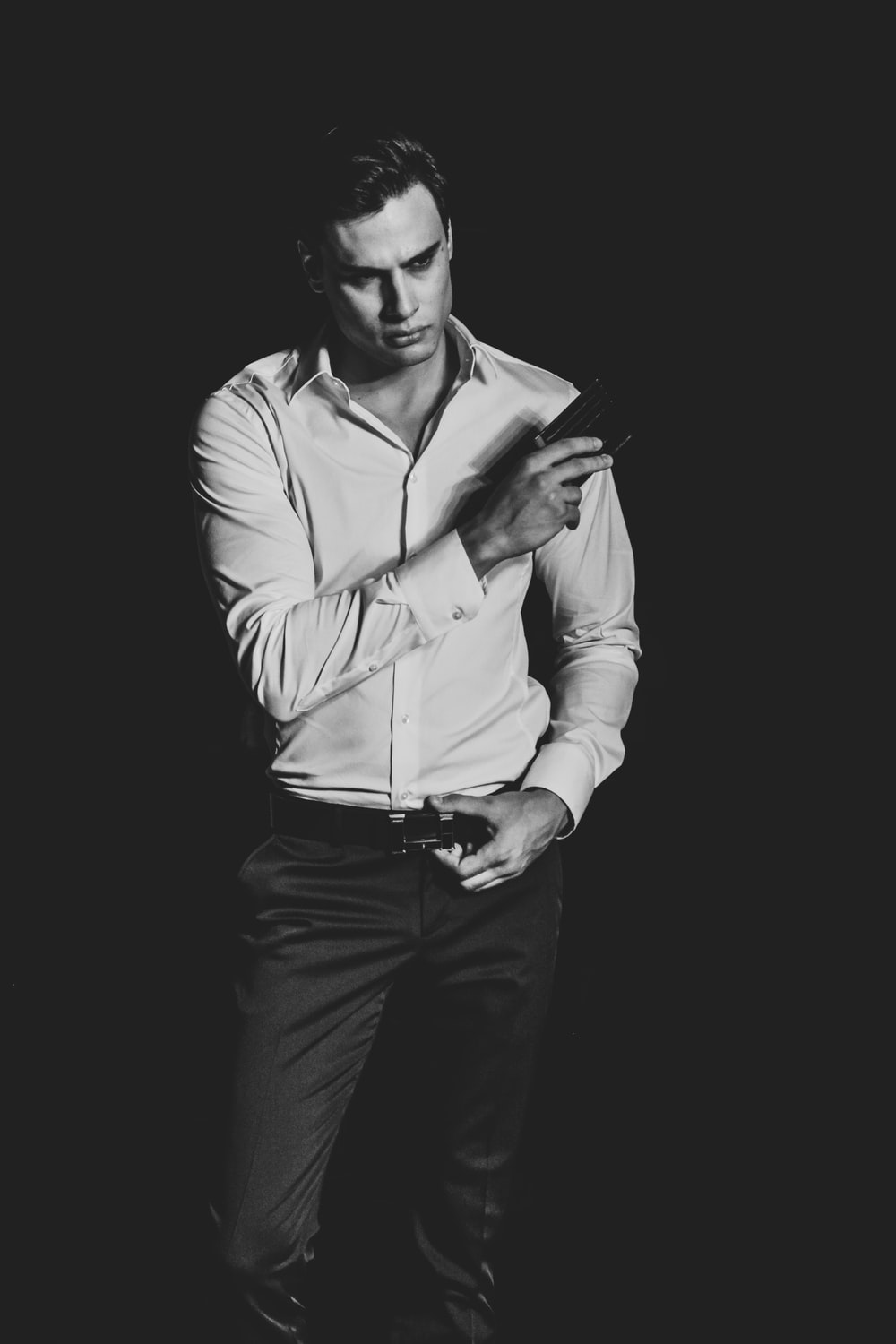 grayscale photography of man holding his belt