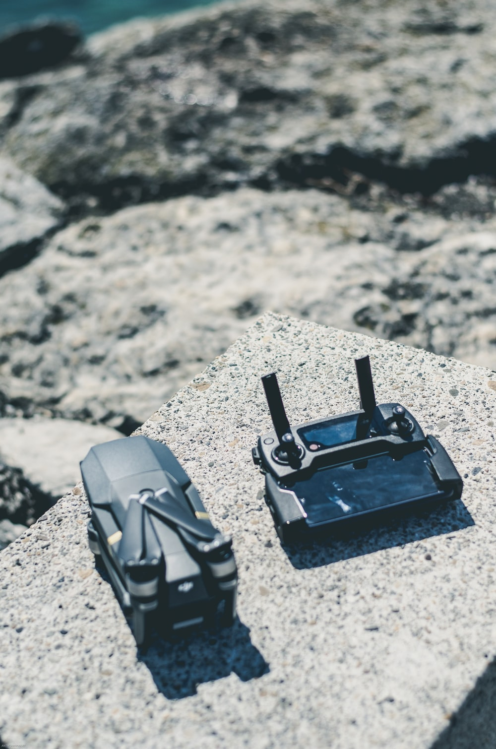 black DJI Mavic drone and controller on platform concrete