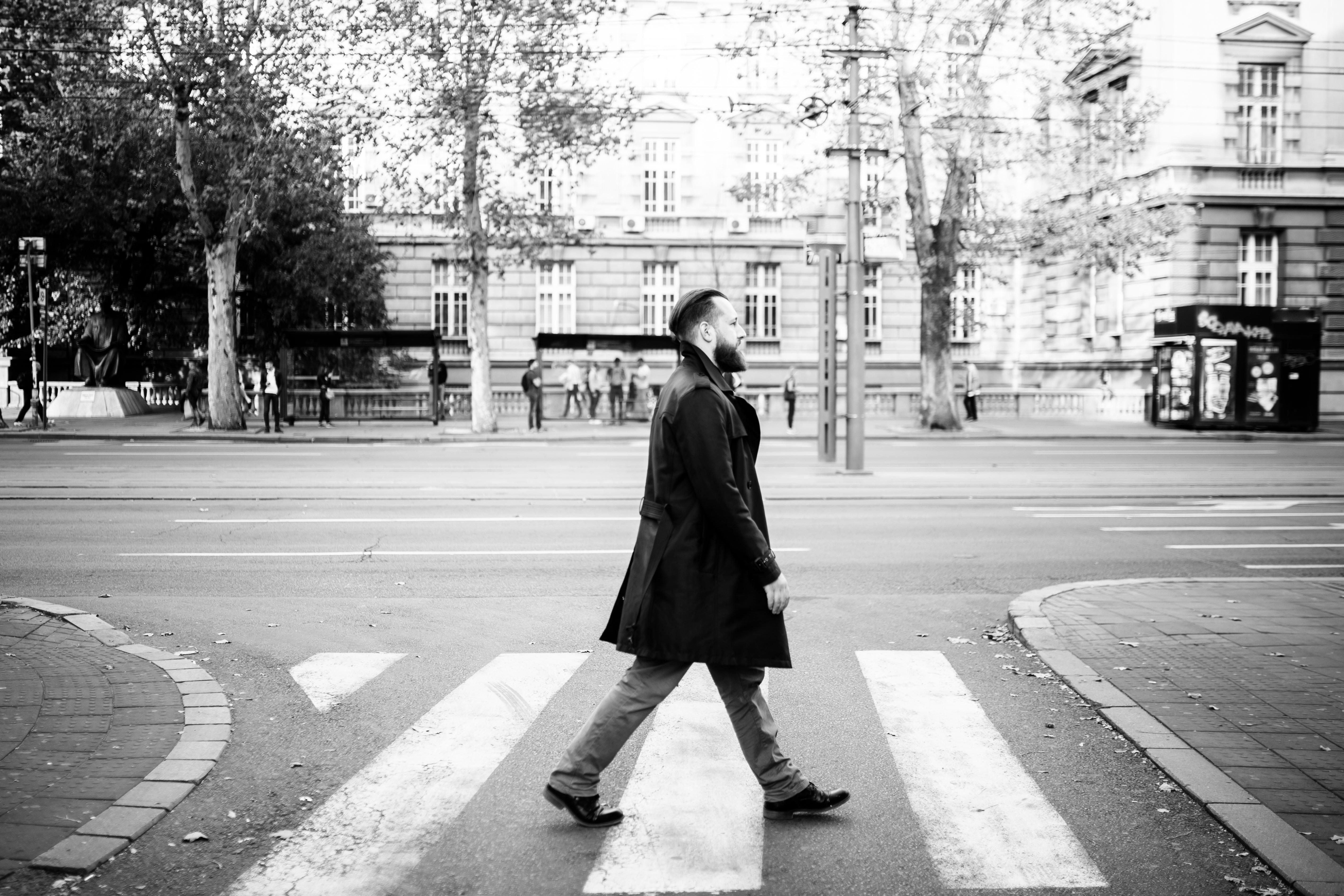greyscale photo of man walking in pedestrian