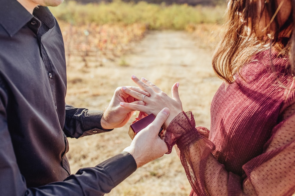 man putting ring in woman's hand