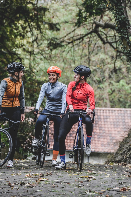 three people riding bike near trees during daytime