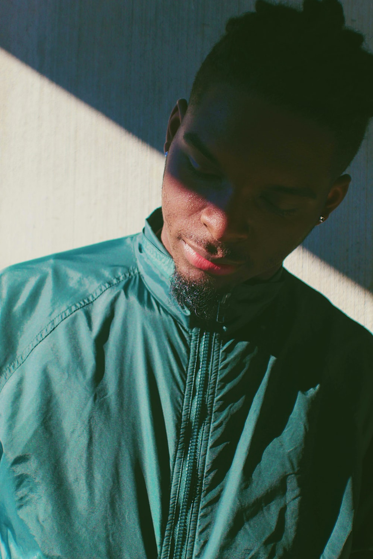 man in green zip-up windbreaker