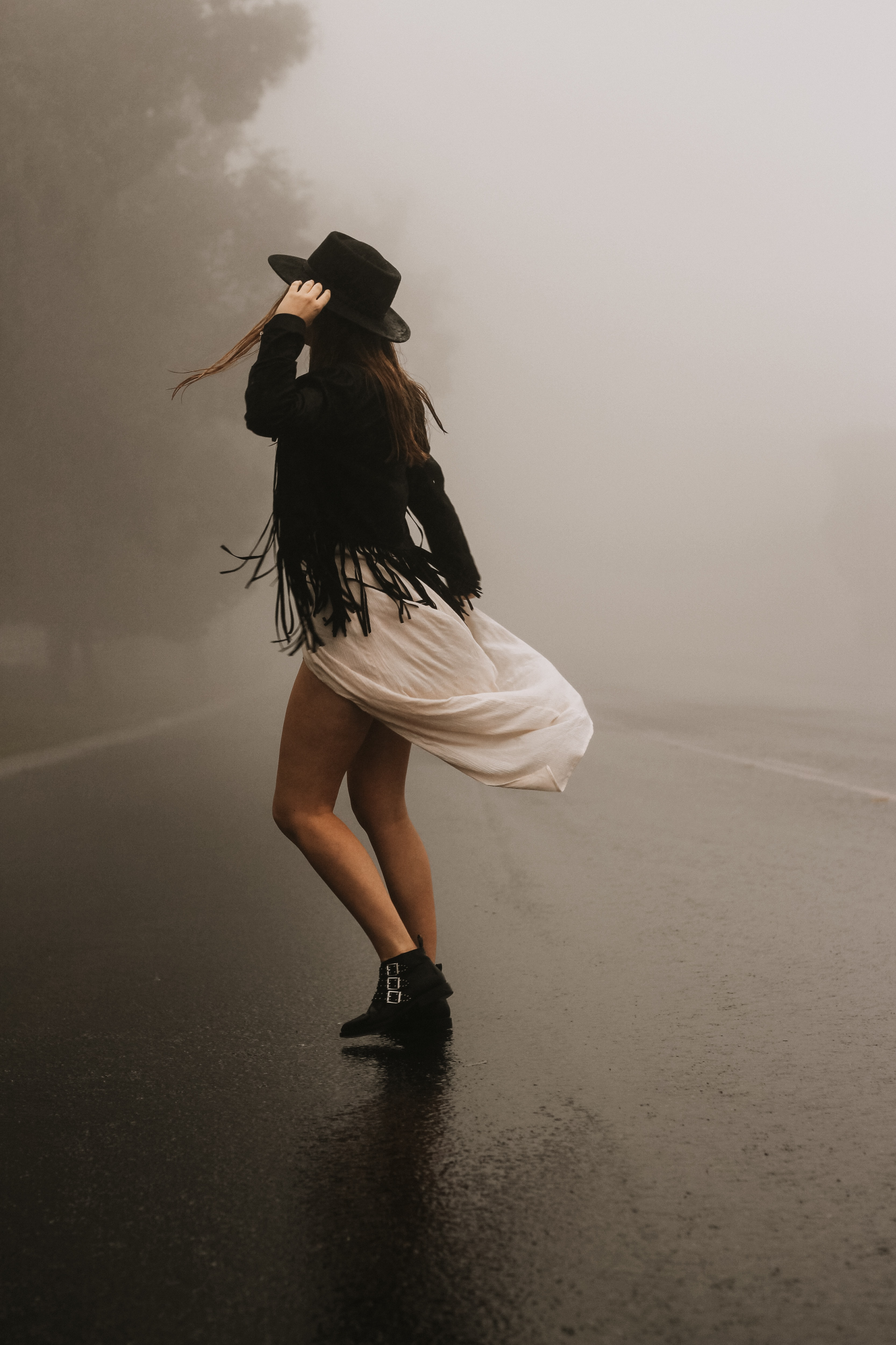 woman wearing black fringe jacket and white dress standing on foggy road